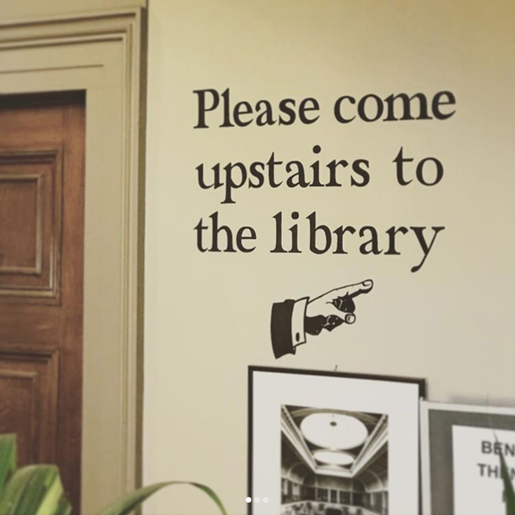 please come upstairs to the library signage
