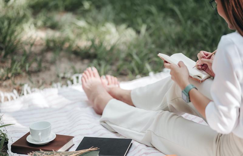 summer woman journalling notebooks midyear review