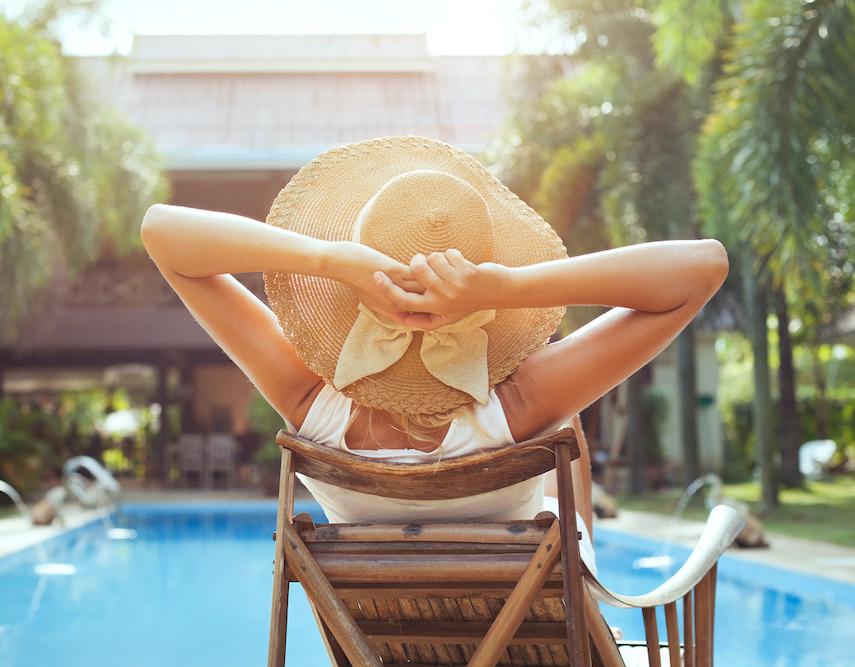 woman lying by sunny poolside relaxing.jpg